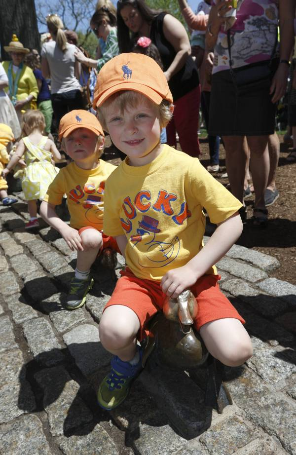 Children play on Make Way for Ducklings scupture at end of parade